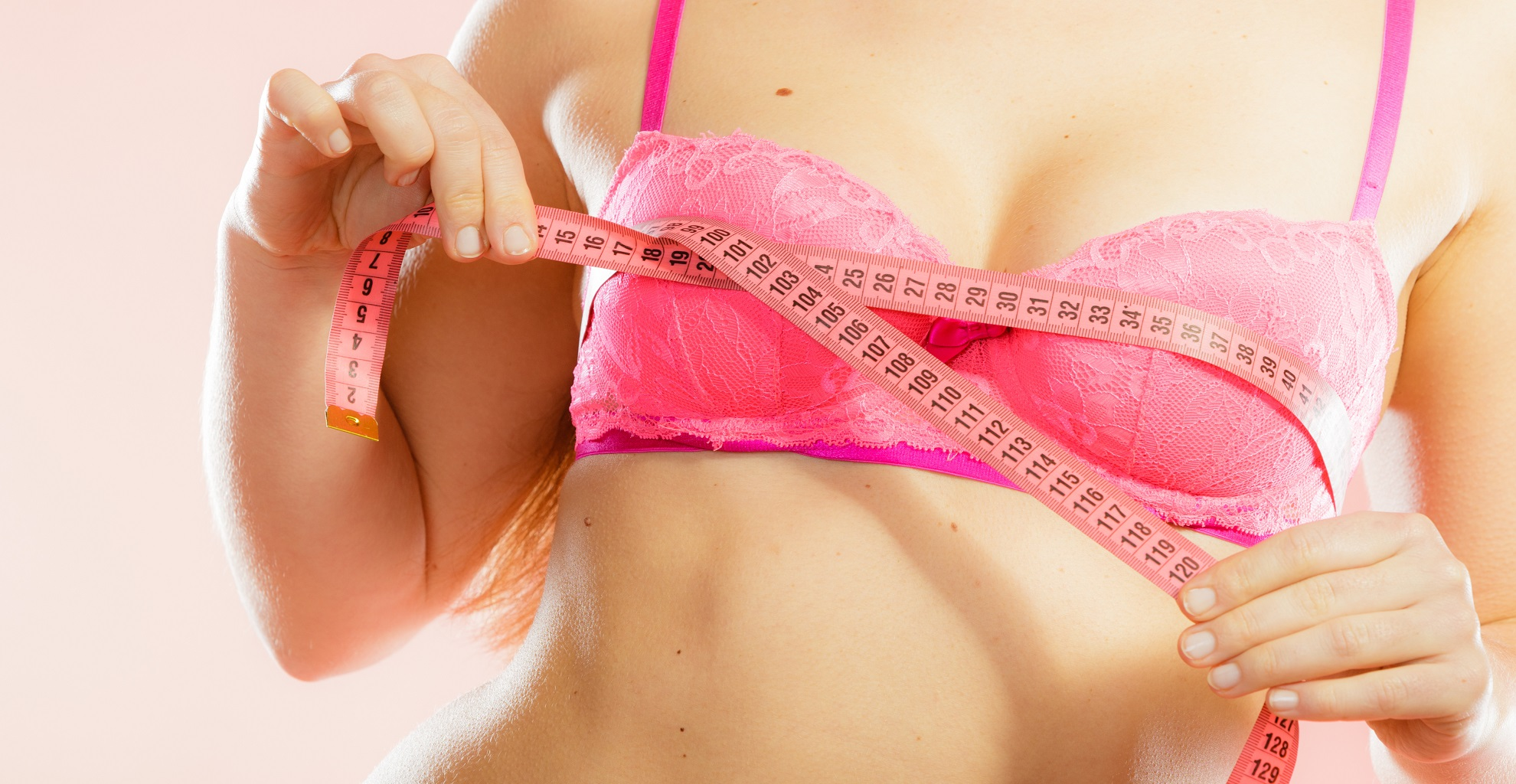 Closeup of female body. Fitness woman fit girl in pink lingerie with measure tape measuring her chest breasts