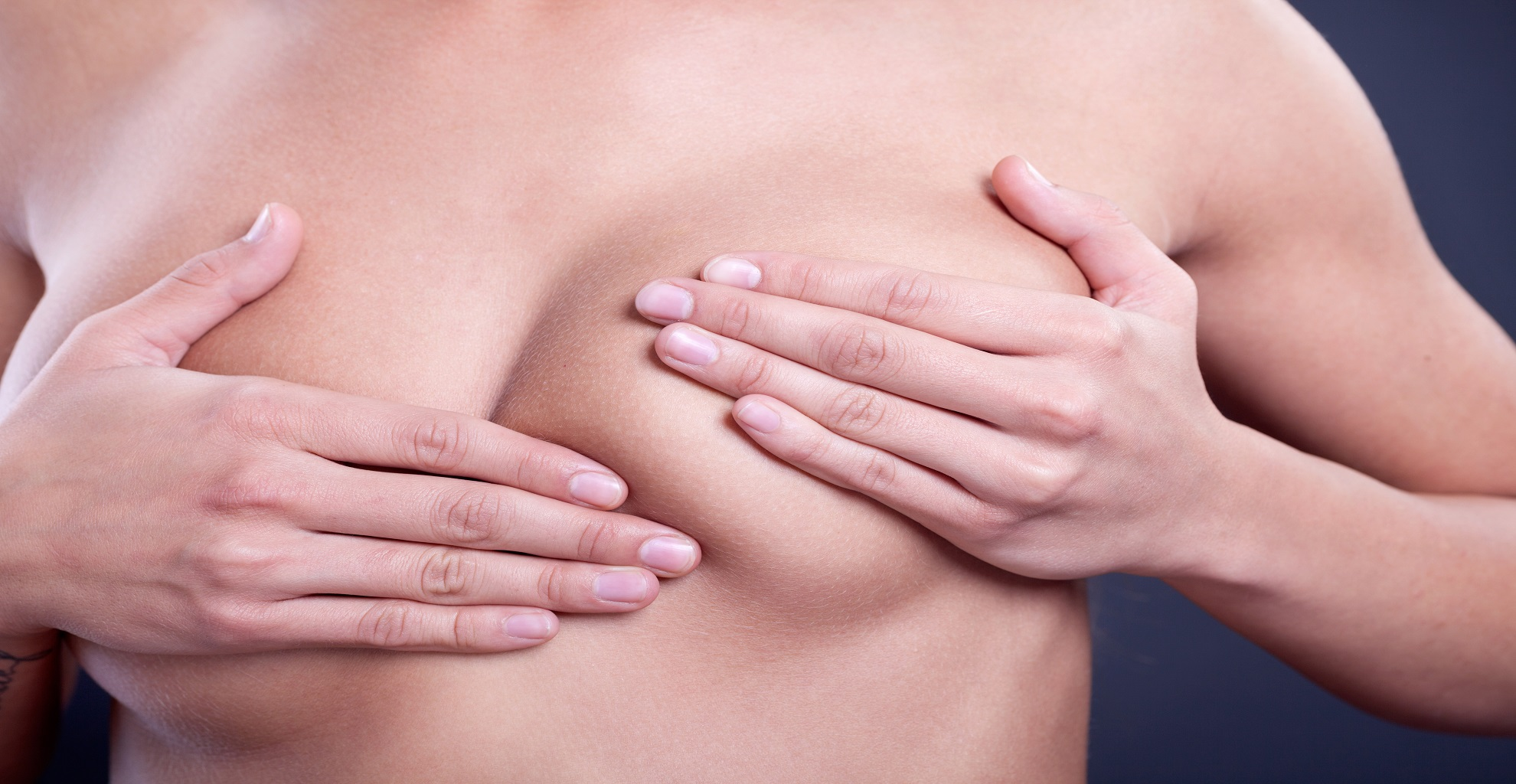 Caucasian adult woman examining her breast for lumps or signs of breast cancer
